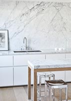 Marble splash back and worktops in white modern kitchen