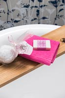 Pink towel on wooden bathroom shelf with toiletries