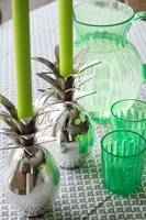 Green glassware and silver novelty candle holders on dining table