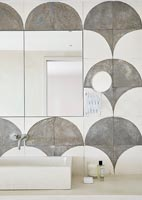Stone cut out feature wall around sink in modern bathroom