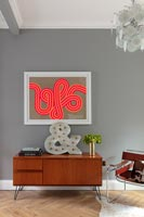 Vintage sideboard and colourful artwork in modern living room