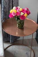 Vase of roses on copper table
