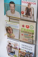Wire wall mounted rack with recipe books in modern kitchen