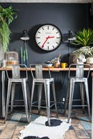 Metal bar stools at breakfast bar with black painted wall