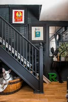 Pet dog in barrel bed under black painted staircase