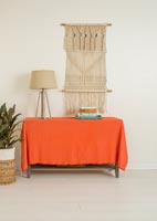 Orange blanket over sideboard with macrame wall hanging
