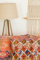 Patterned orange cushions with lamp and macrame wall hanging behind