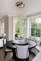 Monochrome dining area with built in window seat