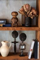 Wooden bookshelves with African ornaments and dried flowers