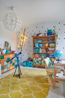 Colourful playroom with spotty feature wall and decorative lights