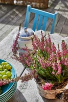 Potted heather on rustic wooden garden table - detail