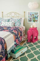 Eclectic colourful bedroom with elephant shaped bedside table