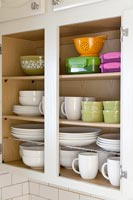 Kitchen cupboard full of crockery and storage boxes