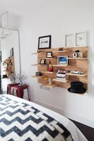 Wooden wall mounted shelving unit on bedroom wall