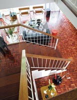 View down modern staircase to open plan living space with parquet floor