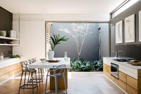 Island in contemporary kitchen-diner with courtyard