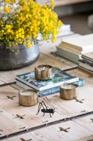 Metal bug and tealights on wooden coffee table