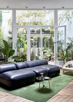 Leather divan sofa in modern living room with view to courtyard garden
