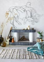 Fireplace with Bull sculpture on wall, guitars and rug