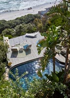Overhead view of swimming pool and decked outdoor living area by sea