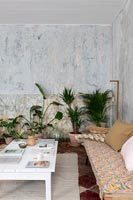 Country living room with bare plaster walls and houseplants