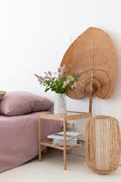 Sisal fan behind wooden bedside table in country bedroom