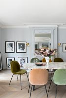 Different coloured chairs around marble dining table
