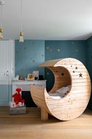 Wooden moon shaped cot bed in modern childrens bedroom