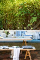 Wooden outdoor dining table and built-in bench seat covered in cushions