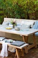 Wooden outdoor dining table with built-in bench seat covered in cushions