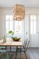 Wicker lampshade over dining table with vintage chairs