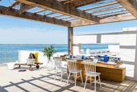 Outdoor dining area on decking overlooking sea