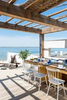 Dining area on decking overlooking the sea