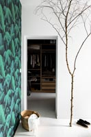 Large bare tree branch in white bedroom next to doorway to dressing room