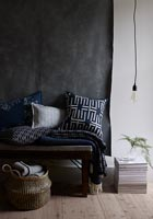 Black and white soft furnishings against black fabric wall hanging