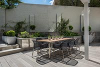 Outdoor dining area on terrace of walled courtyard garden