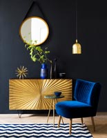 Gold sideboard and blue chair in black painted living room
