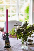 Candle and flowers on country dining table