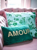 Colourful cushions on pink sofa
