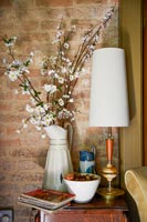 White enamel vase filled with branches of blossom on side table