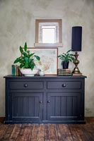 Black wooden sideboard in country living room with bare plaster wall