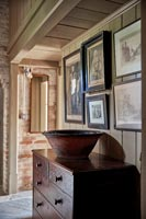 Chest of drawers and old photographs in country hallway