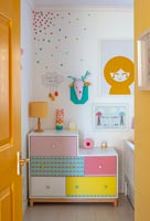 Colourful chest of drawers and artwork in childrens room