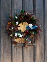 Wreath on wooden front door with modern decorations and fairy lights