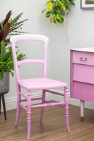Chair painted to create an ombre paint effect with various shades of pink