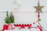 Table decorated for Christmas with wooden red advent candle light