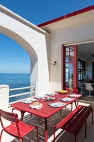 Outdoor dining table laid for lunch on red and white terrace with sea views