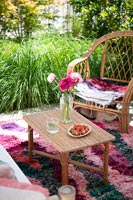 Cane furniture and colourful rug in outdoor living area