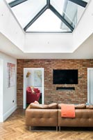 Exposed brick wall with wall mounted television and leather sofa