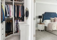 View of clothing hanging in large bedroom wardrobes